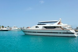 A white motor yacht is moored in the azure waters of the Red Sea in the harbor of Hurghada. Clear blue skies echo the color of the sea