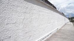 A white wall in perspective to that of a street.