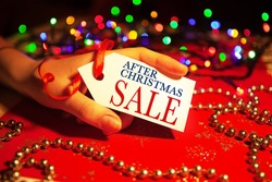 A woman's hand holds a label with the text - after Christmas sale, on a decorated Christmas background, during the Christmas and New Year holidays.