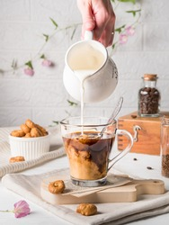A woman's hand pours milk from a white milk jug into a glass mug with black coffee. Mixing products. Morning breakfast with dry small bagels and coffee in the kitchen on a background of white tiles.
