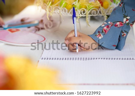 A woman's hand writing a greeting on a wedding greeting book