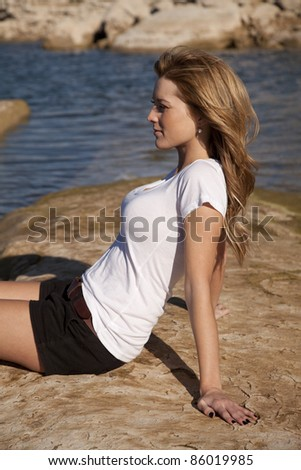 A woman sitting on a rock by the ocean relaxing and enjoying the warmth.
