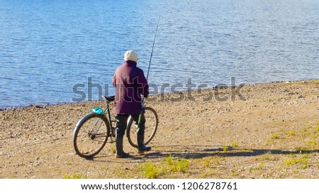 A woman walks along the river carries a Bicycle and carries a fishing rod                             #1206278761