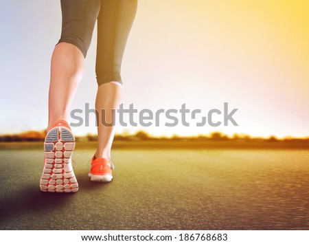 a woman with an athletic pair of legs going for a jog or run during sunrise or sunset healthy lifestyle concept done with an instagram like filter