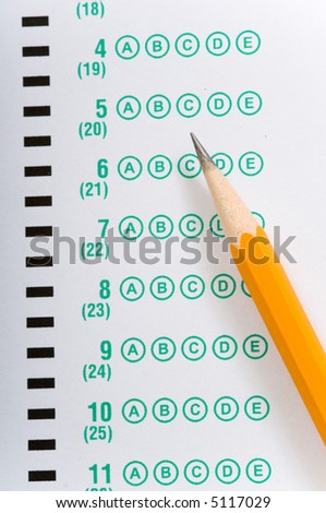 a yellow pencil lying on a multiple choice test or exam answer sheet