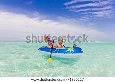 A young boy and girl in a rubber raft near a tropical beach. - stock photo