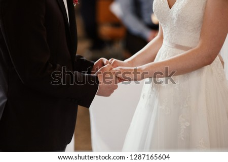 a young couple holding hands in a church #1287165604