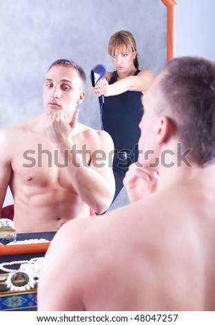 A young couple sharing a bathroom, the angry woman waiting for her place in front of the mirror and try to shot him with fan, focus on woman