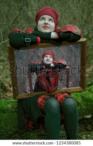 a young girl in a red beret, a black coat and a skirt in a cage in the woods in autumn keeps her photo in a wooden frame. Concept psychology, narcissism