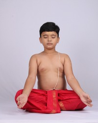 A young indian cute kid doing yoga over white background, wearing a dhoti. Meditation pose.