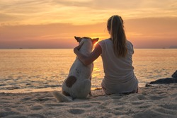 A young woman with a dog watching the sunset on the beach