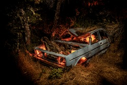 abandoned car in the field at night