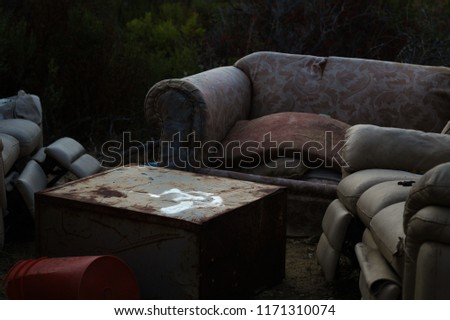 3 abandoned couches in the woods with a table in between. Found in the cuts of San Mateo county. #1171310074