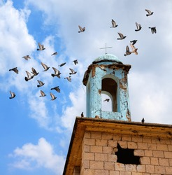 Abandoned destroyed stone building of a Christian church. Old brick wall. Cracked and shabby blue dome with cross. Flock of pigeons flies on the bright cloudy sky over the church. Oblivion