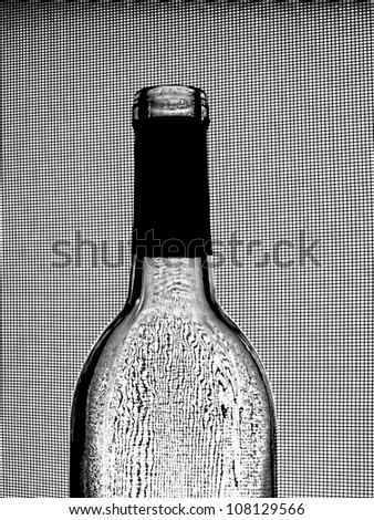 Abstract black and white background design made from an empty  wine bottle against a wire window screen.