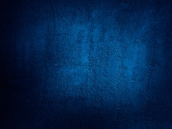 Abstract blue background. Dark blue grunge background. Rough grainy concrete wall surface texture. Deep blue concrete backdrop.