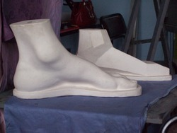academic setting two  plaster feet on a table with drapery