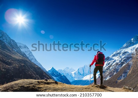 Active hiker hiking, enjoying the view, looking at mountain Himalaya landscape. mountaineering sport lifestyle concept #210357700