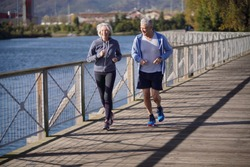Active senior couple jogging together on bridge