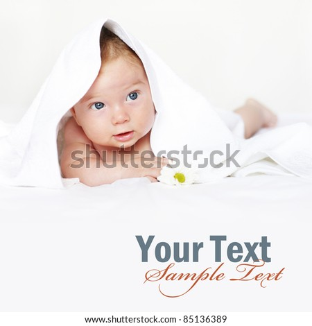 Adorable baby under white towel with copy space