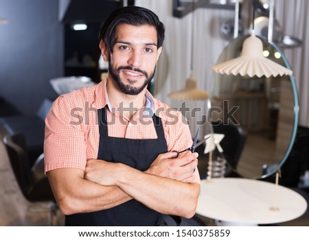 Adult cheerful male hairdresser working in hairdressing salon