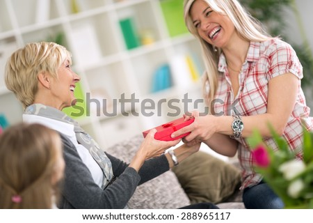 Adult daughter giving to her mother gift for Mother\'s Day while little girl looking