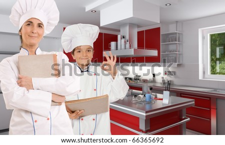 Adult female chef with a child cook in a kitchen interior