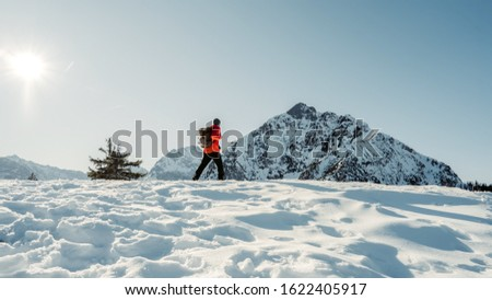 Adventurous man are hiking to the top of a mountain during a vibrant winter sunset. Extreme winter mountaineering. Adventure ascent.