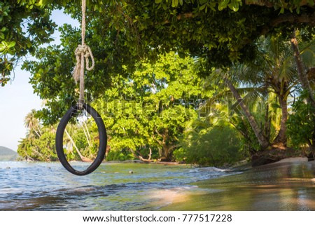 \nAdvertising,Travel, Vacation and Holiday Concept -  Beautiful beach. Tire swing hang under a tree and Bubble of Sea wave on the beach in exotic travel destinations.