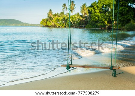 \nAdvertising,Travel, Vacation and Holiday Concept -  Beautiful beach. Wooden swing hang under a tree and Bubble of Sea wave on the beach in exotic travel destinations.