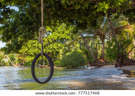 \nAdvertising,Travel, Vacation and Holiday Concept - View of the sea beach and Tire swing hang under a tree with Bubble of Sea wave on the beach.