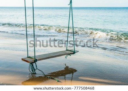 \nAdvertising,Travel, Vacation and Holiday Concept - View of the sea beach and Wooden swing hang under a tree with Bubble of Sea wave on the beach.