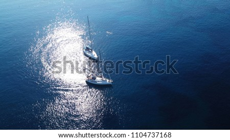 Aerial drone bird's eye view of luxury sail boats docked in deep blue Aegean sea
