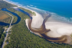 Aerial image of river waters cutting through vegetation and meeting the ocean. Itaguaré beach. Beautiful landscape made by drone from a tourist location. Amazon rainforest. Environmental preservation