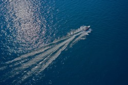 Aerial view of a boat in motion on blue water. Top view of a white boat sailing in the blue sea. luxury motor boat. Drone view of a boat sailing at high speed.
