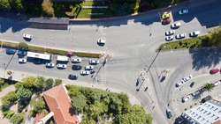 Aerial view of the crosswalk and road junction between buildings at the city center. Vehicles are waiting in red light and pedestrians are crossing the street.