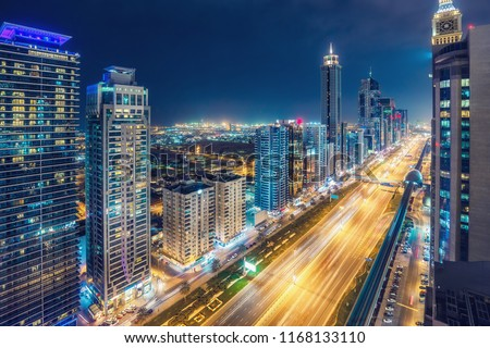 Aerial view on downtown Dubai, UAE with highways and skyscrapers. Scenic nighttime skyline. #1168133110