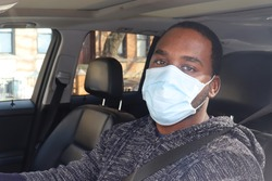 African American Man Driving car wearing medical mask