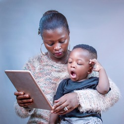 African mother carrying her yawning child on her laps with a smart phone in her hand