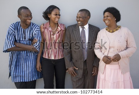 4 African people standing together against a wall with happy expressions. Thye look like family.