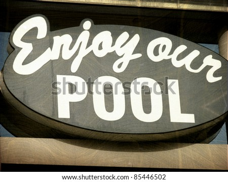 aged and worn vintage photo of enjoy our pool roadside motel sign