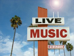 aged and worn vintage photo of live music sign with palm trees and bright sun