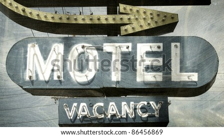 aged and worn vintage photo of motel sign with arrow