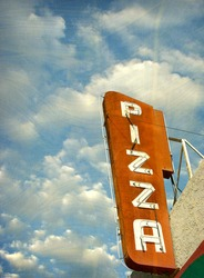 aged and worn vintage photo of neon pizza sign