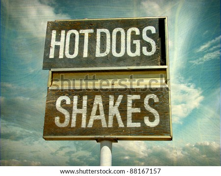 aged and worn vintage photo of old retro diner hot dogs and shakes sign