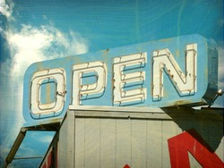 aged and worn vintage photo of open sign