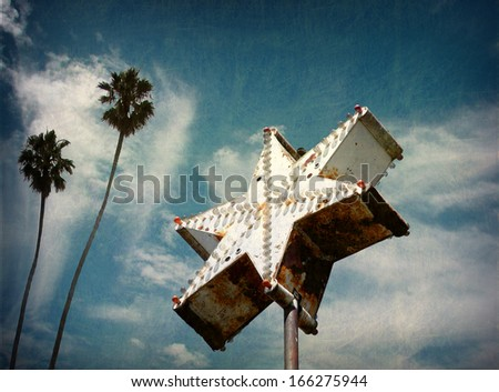 aged and worn vintage star neon sign with palm trees