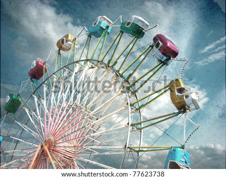 aged vintage photo of carnival ferris wheel with beautiful cloudy sky