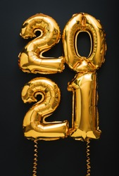 2021 air balloon gold text with ribbons on black background. Happy New year eve invitation with Christmas gold foil balloons 2021. vertical.