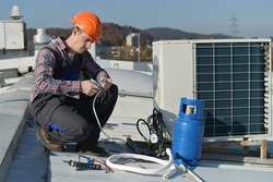Air Conditioning Repair, young repairman on the roof fixing air conditioning system. Model is actual electrician.